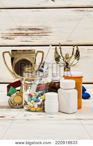 Champion's trophies and illegal medications. Lots of pills and syringe. Doping issues in sports.