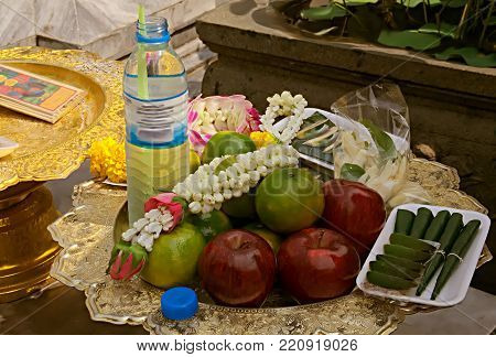 Symbolic offerings of food, fruit, drinks and flowers in a temple, Bangkok, Thailand.