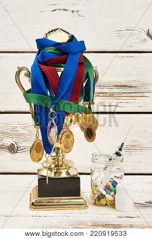 Trophy won by unfair play. Medals on champion cup and prohibited medications on wooden table. Deceit, doping scandal.
