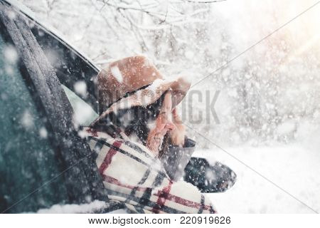 Happy and smiling hipster girl sitting in car and looking from a window enjoying winter landscape. Pretty woman wearing hat and poncho hanging out of the car window and  having fun under snowfall