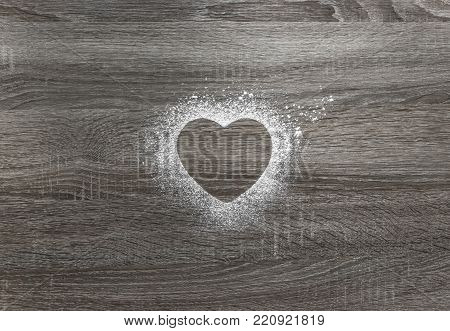 on a wooden background with powdered powder snow a silhouette of the heart