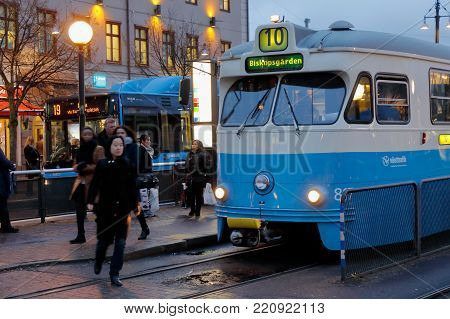 Gothenburg, Sweden - November 1, 2017: A tram has stoped at the tram stop Kungstorget i downtown Gothenborg and woman crossing the tracks in front of the vehicle during the evening.