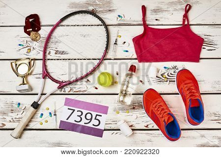 Awards, equipment and doping drugs of a tennis player. Uniform and number on wooden table. Cheating to get the first place.