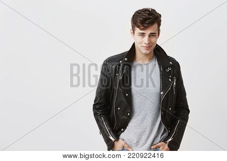 Handsome confident good-looking male model dressed in trendy black leather jacket over gray t-shirt, looking at camera with his blue appealing eyes, posing against gray background.