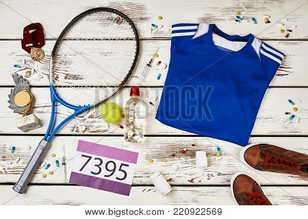 Racquet, shirt, sneakers and number on wooden table. Tennis equipment, awards and spilled drugs. Usage of doping, cheating in sports.