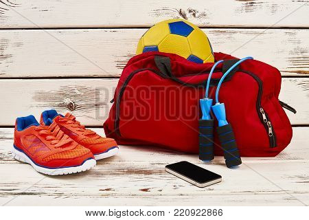 Sneakers, mobile phone and equipment. Jumping rope and soccer ball in gym bag. Locker room concept.