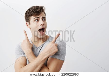 Astonished excited positive young male with dark hair tips, points at copy space with fore fingers advertises something, keeps mouth widely opened. People, advertising, surprisment concept
