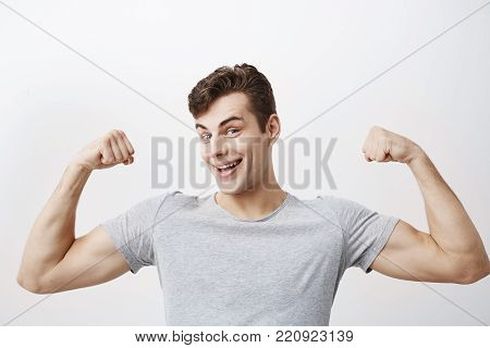 Positive emotional young man, dressed casually, smiles broadly, shows muscles on his arms, feels proud to be strong and have strength, says: I am hero. Muscular male athlete raises arms with joy, shows how strong he is.