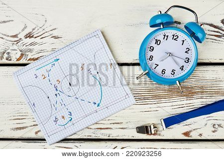 Development of game strategy. Notebook with drawn tactics, whistle and table clock. Work of football coach.