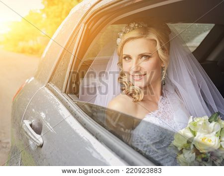 close-up portrait of a pretty shy bride in a car window