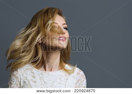 Portrait of a happy adult blonde woman spinning her head, grey background