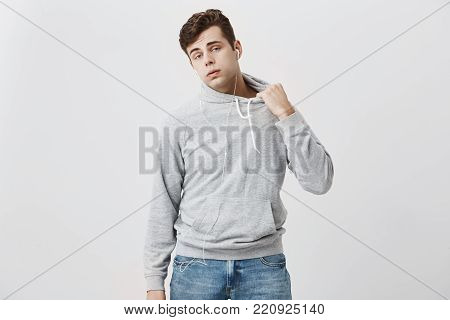 Attractive young caucasian male student in gray hoodie and jeans, puffing out his cheeks, like he is tired of running as he is late for classes. Dark-haired stylish man posing against gray background.