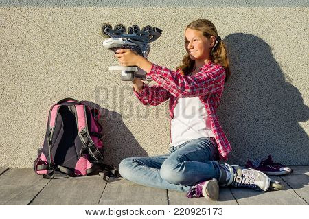 Girl teen sits on a wall background, holds a roller