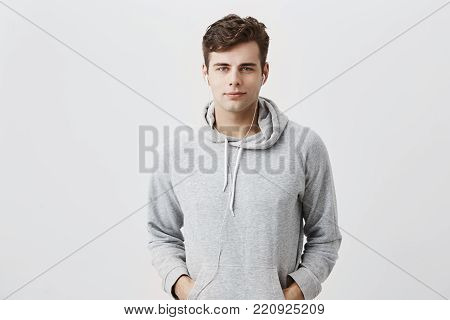 Handsome attractive European young man in gray hoodie, with hands in pockets, look pleased at camera, has good mood as comes home after work. Fashionable pleasant looking male student poses against gray studio wall.