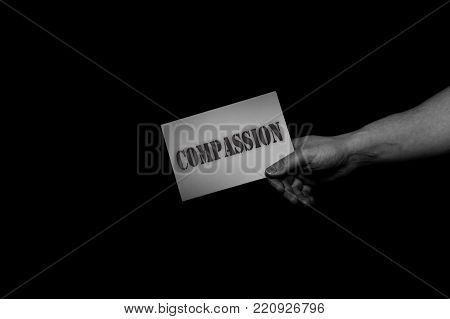 Compassion, helping hands concept, offering care, love, hope and support. a hand holding a card isolated black and white