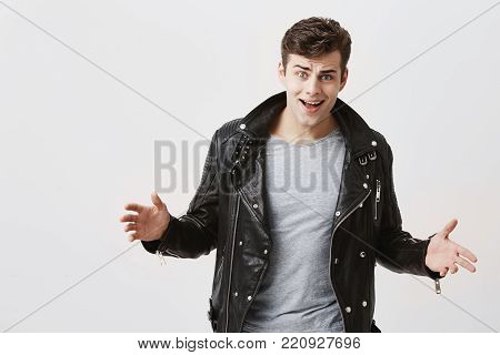 Annoyed attractive male gestures with irritation, keeping palms opened, dressed in black leather jacket and jeans, frowns face bacause of miscommunication isolated against gray background. Negative human emotions and reaction.
