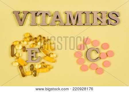 Vitamins And Supplements. Vitamin C, E. Background yellow, fish oil capsules and vitamin C vials