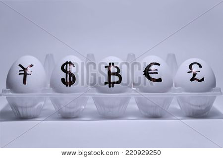 The inscriptions of the symbols of five national currencies on chicken eggs. Chicken eggs are located in a transparent package. Eggshell white. Yen, dollar, bitcoin, euro, pound sterling.