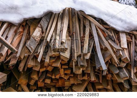 snow covered chopped firewood background. conceptual fuel imagery