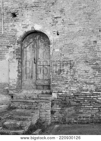 Old wooden door in old brick wall. Black and white photo