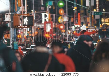 A crowd moves through Times Square - a lot of people, telephoto shot