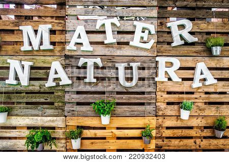 mater natura mother nature text green thumb pallets wooden background .