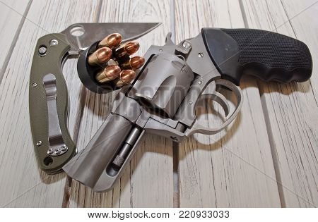 An opened folding knife with a green handle along with a loaded speed loader and a stainless steel revolver placed on a white wooden table
