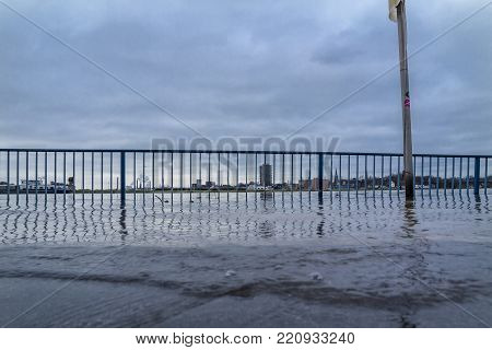 The river Rhine is flooding the promenade with handrail