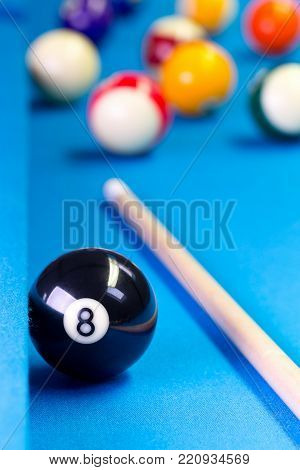 Billiard pool game eight ball with eightball balls and cue on billiard table with blue cloth, selective focus on eight ball