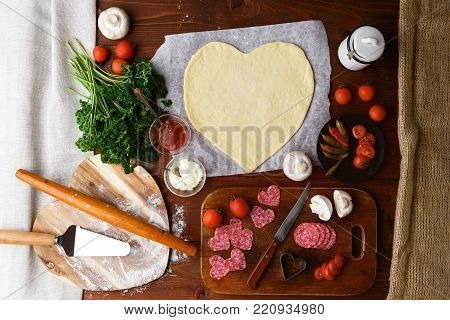 The Chef Makes A Pizza Heart For The Valentine's Day Holiday. Classic Italian Pizza With Salami And