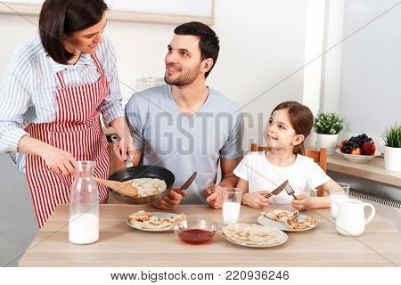 Photo of hard working wife, husband and their daughter sit together at kitchen table, going to eat delicious pancakes, enjoy togetherness. Friendly family eat breakfast, appetizing flannel cake