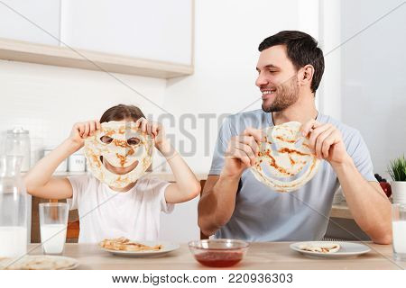 Image of cheerful small girl covers face with pancake, sits near her affectionate father at kitchen, have tasty supper together, enjoy dessert prepared by mother. Culinary and family concept
