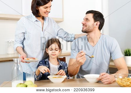 Three family members have delicious healthy breakfast at kitchen, eat cornflakes with milk, enjoy togetherness and domestic atmosphere. Husband looks with love at wife, satisfied with tasty dish
