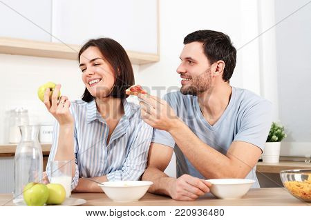 Happy couple spend free time or weekend together at kitchen, glad husband suggests wife to eat snack, she refuses as eats green apple, have breakfast. Family, cooking and relations concept