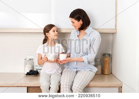 Shot of cheerful mother and daughter sit together at kitchen table, drink hot tea in morning, have pleasant friendly talk between each other. Curious girl asks something in mum during coffee break