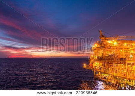 Offshore oil and gas rig platform with beautiful sunset time or twilight time in the gulf of Thailand for business industrial concept.