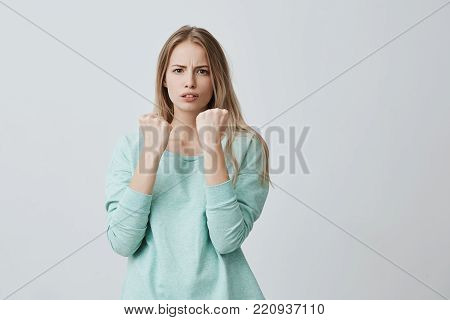 Defence and protection concept. Strong sport woman wearing casual clothes with blonde hair having serious and confident look keeping fists clenched in front of her defending herself from offence and bad treatment