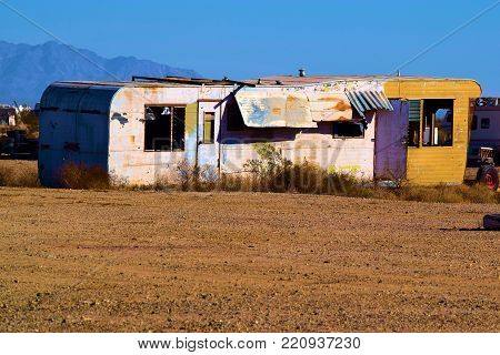 Forgotten landscape including an abandoned collapsing trailer taken in Slab City, CA