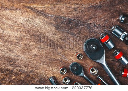 Top view of Working tools,wrench,socket wrench,hammer,screwdriver,plier,electric drill,tape measure,machinist square and safety glasses on wooden background.flat lay design for construction concept.