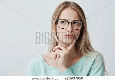 Indoor shot of thoughtful pretty woman has long blonde hair with stylish eyewear, looks aside with pensive expressions, plans something on coming weekends, poses against blank copy space. Puzzled female