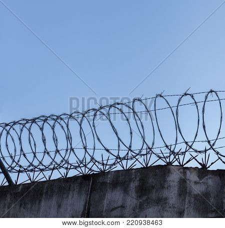 Barbed wire spiral on top of rough high stone wall on the sky background Stock photo