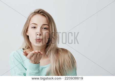 Portrait of young attractive caucasian woman posing with kiss on her lips with blonde dyed hair, having flirty look feeling confident and beautiful. Charming female model sending kisses to camera, saying goodbye