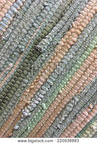 Cloth sewn from strips of fabric. Needlework, reuse of materials. Gray, green, and orange strips of fabric pastel colors. Textile background.