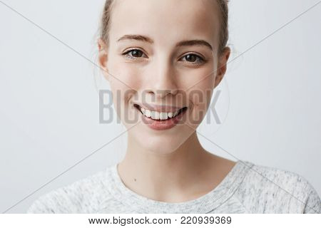 Close-up shot of beautiful positive caucasian female with dark appealing eyes and healthy pure skin, smiling broadly at camera demonstrating her white perfect teeth, isolated against gray studio background