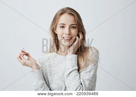 Music, happiness and technology concept. Lovely beautiful female wears her long blonde hair loose with white earphones, listens to music on cell phone, uses music app, poses against gray wall with copy space for promotional text