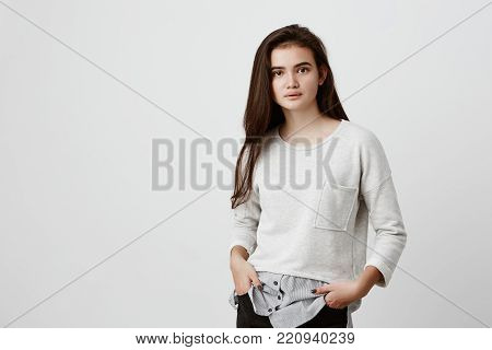 Horizontal portrait of beautiful teenage girl hair having oval face, dark attractive eyes and long straight dark hair dressed casually feeling relaxed while standing with hands in pockets, posing indoors