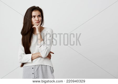 Pretty young female with long dark hair looking away wearing loose casual clothes holding hand under her chin, building plans, thinking about something. Pensive brunette beautiful girl with thoughtful and pensive face expression