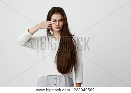 Indoor shot of pretty brunette girl with dark long hair, making faces, pouting lips, closing one of her eyes with v sign, having pleased expression. Beautiful young female dressed in casual clothes, mocking, posing indoors poster