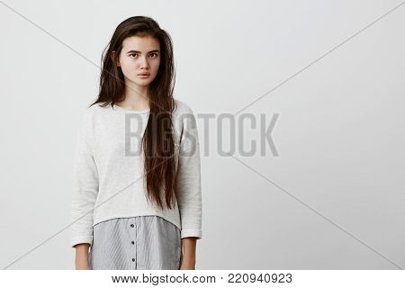Human face expressions and emotions. Thoughtful young beautiful female with dark long straight hair in casual clothing pensively and calmly looking at camera. Beauty, youth and tenderness concept