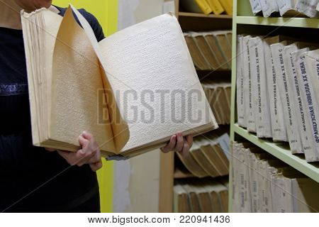 ST. PETERSBURG, RUSSIA - NOVEMBER 22, 2016: Staff of the St. Petersburg state library for the blind and visually impaired people demonstrating the Braille book during the program Tactile Library